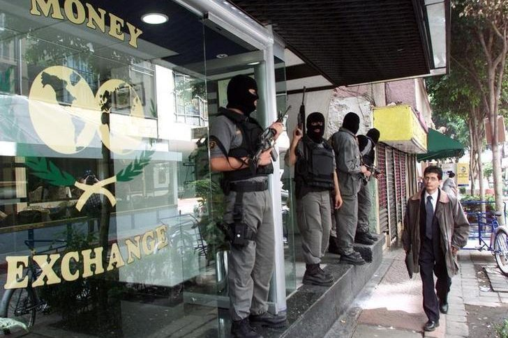 "A pedestrian looks over at masked, and heavily armed, Mexican Federal agents as they stand guard, June 21, 2001, outside a Mexican money changing house during raids on properties in the capital linked to yesterday's DEA ""Operation Marquis"" in which tons of narcotics and over two hundred suspects were arrested in an attempt to close down a large cocaine smuggling operation allegedly linked to the Juarez cartel."